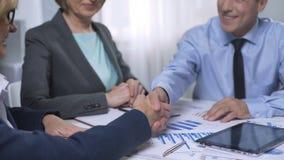 Rappresentanti maschii della società delle signore di riunione dell'investitore, discutenti il contratto stock footage