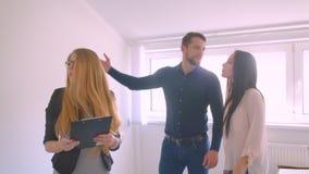 Rappresentazione caucasica femminile di agente immobiliare e descrivere l'appartamento ai suoi giovani clienti caucasici