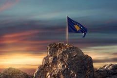 rappresentazione 3d dell'ondeggiamento della bandiera del Kosovo su paesaggio roccioso al celebra Fotografie Stock Libere da Diritti