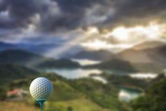 rappresentazione 3d della palla da golf sul T sopra un verde vago Fotografia Stock