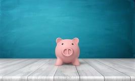 rappresentazione 3d di un porcellino salvadanaio rosa nella vista frontale che sta su una tavola di legno Fotografie Stock Libere da Diritti
