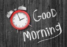 rappresentazione 3d di una vista superiore su una retro sveglia rossa che si trova su un fondo di legno vicino ad un buongiorno b Fotografie Stock Libere da Diritti