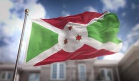 Rappresentazione della bandiera 3D del Burundi sul fondo della costruzione del cielo blu Immagine Stock Libera da Diritti