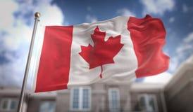Rappresentazione della bandiera 3D del Canada sul fondo della costruzione del cielo blu Fotografia Stock