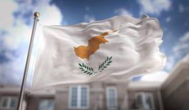 Rappresentazione della bandiera 3D del Cipro sul fondo della costruzione del cielo blu Fotografia Stock