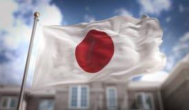 Rappresentazione della bandiera 3D del Giappone sul fondo della costruzione del cielo blu Fotografia Stock