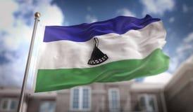 Rappresentazione della bandiera 3D del Lesotho sul fondo della costruzione del cielo blu Immagine Stock Libera da Diritti