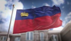 Rappresentazione della bandiera 3D del Liechtenstein sul fondo della costruzione del cielo blu Fotografie Stock