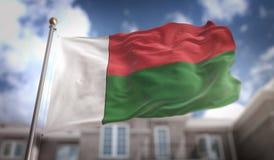 Rappresentazione della bandiera 3D del Madagascar sul fondo della costruzione del cielo blu Immagini Stock