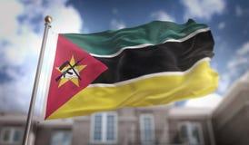 Rappresentazione della bandiera 3D del Mozambico sul fondo della costruzione del cielo blu Immagini Stock Libere da Diritti