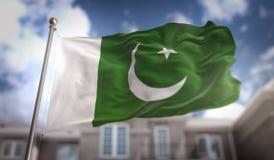 Rappresentazione della bandiera 3D del Pakistan sul fondo della costruzione del cielo blu Immagine Stock