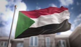 Rappresentazione della bandiera 3D del Sudan sul fondo della costruzione del cielo blu Immagine Stock