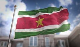 Rappresentazione della bandiera 3D del Surinam sul fondo della costruzione del cielo blu Fotografia Stock Libera da Diritti