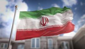 Rappresentazione della bandiera 3D dell'Iran sul fondo della costruzione del cielo blu Fotografia Stock Libera da Diritti