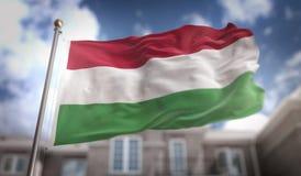 Rappresentazione della bandiera 3D dell'Ungheria sul fondo della costruzione del cielo blu Immagini Stock
