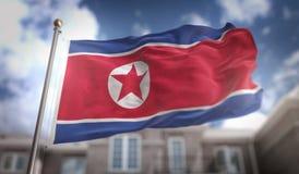 Rappresentazione della bandiera 3D della Corea del Nord sul fondo della costruzione del cielo blu Immagine Stock