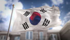 Rappresentazione della bandiera 3D della Corea del Sud sul fondo della costruzione del cielo blu Immagine Stock Libera da Diritti