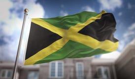 Rappresentazione della bandiera 3D della Giamaica sul fondo della costruzione del cielo blu Fotografia Stock