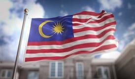 Rappresentazione della bandiera 3D della Malesia sul fondo della costruzione del cielo blu Fotografia Stock