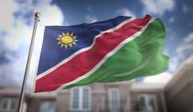 Rappresentazione della bandiera 3D della Namibia sul fondo della costruzione del cielo blu Fotografia Stock Libera da Diritti
