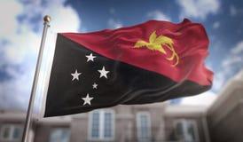 Rappresentazione della bandiera 3D della Papuasia Nuova Guinea sul cielo blu che costruisce Backgrou Immagine Stock