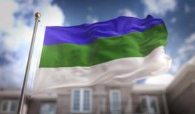 Rappresentazione della bandiera 3D della Repubblica del Komi sul fondo della costruzione del cielo blu Fotografia Stock