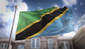 Rappresentazione della bandiera 3D della Tanzania sul fondo della costruzione del cielo blu Fotografia Stock