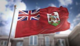 Rappresentazione della bandiera 3D delle Bermude sul fondo della costruzione del cielo blu Fotografie Stock