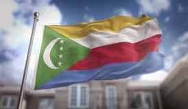 Rappresentazione della bandiera 3D delle Comore sul fondo della costruzione del cielo blu Fotografia Stock Libera da Diritti