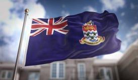 Rappresentazione della bandiera 3D delle Isole Cayman sul fondo della costruzione del cielo blu Immagine Stock