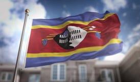 Rappresentazione della bandiera 3D dello Swaziland sul fondo della costruzione del cielo blu Fotografia Stock