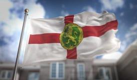 Rappresentazione della bandiera 3D di Alderney sul fondo della costruzione del cielo blu Immagine Stock Libera da Diritti