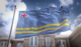 Rappresentazione della bandiera 3D di Aruba sul fondo della costruzione del cielo blu Fotografie Stock