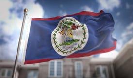 Rappresentazione della bandiera 3D di Belize sul fondo della costruzione del cielo blu Fotografia Stock Libera da Diritti