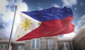 Rappresentazione della bandiera 3D di Filippine sul fondo della costruzione del cielo blu Immagine Stock