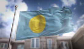 Rappresentazione della bandiera 3D di Palau sul fondo della costruzione del cielo blu Immagine Stock Libera da Diritti