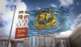 Rappresentazione della bandiera 3D di Saint Pierre e Miquelon sulla costruzione del cielo blu Immagine Stock