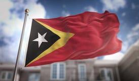 Rappresentazione della bandiera 3D di Timor orientale sul fondo della costruzione del cielo blu Fotografie Stock Libere da Diritti