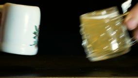Rappresentazione di abuso di alcool, mani che tostano con le piccole tazze piene di birra video d archivio