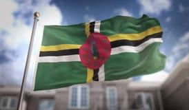Rappresentazione di Dominica Flag 3D sul fondo della costruzione del cielo blu Fotografia Stock Libera da Diritti