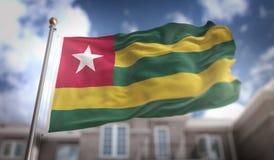 Rappresentazione di Togo Flag 3D sul fondo della costruzione del cielo blu Fotografie Stock Libere da Diritti