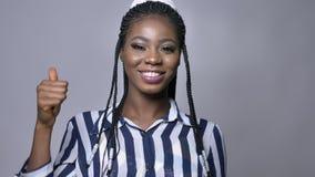 Rappresentazione femminile africana felice sveglia come il gesto ed esaminare macchina fotografica con il sorriso piacevole mentr stock footage
