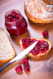 Rapsberry jam with slice of bread. On wooden table Stock Image