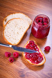 Rapsberry jam with slice of bread. On wooden table Stock Photography