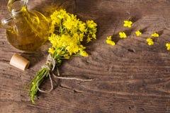 Rapsolja och våldtar blommor på trätabellen Royaltyfria Bilder