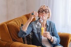 Rapt grandmother blowing through special stick Stock Image