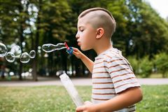 Rapt little boy blows bubbles in the park. Delights of childhood Stock Photography