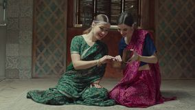 Rapting women in hindu sari looking at jewelry box. Bragging woman showing to female guest jewelry box full of decorations sitting on floor in oriental interior stock video footage