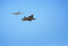 Raptor with P-51. The military Raptor aircraft in flight escorted by a P-51 Stock Photos