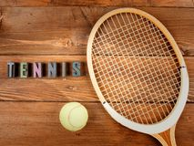 Raquet and ball in wood background. And word tennis in letterpress type stock photography